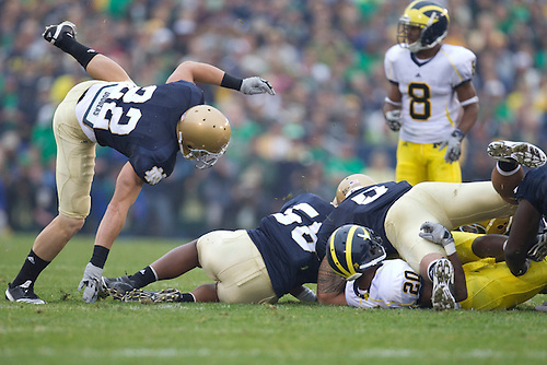 Notre Dame defensive players tackle Michigan running back Michael Shaw (#20) during NCAA football game between the Notre Dame Fighting Irish and the Michigan Wolverines.  Michigan defeated Notre Dame 28-24 in game at Notre Dame Stadium in South Bend, Indiana.