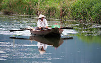 Ninh Binh, women rowing her traditional Boat along a small waterway.