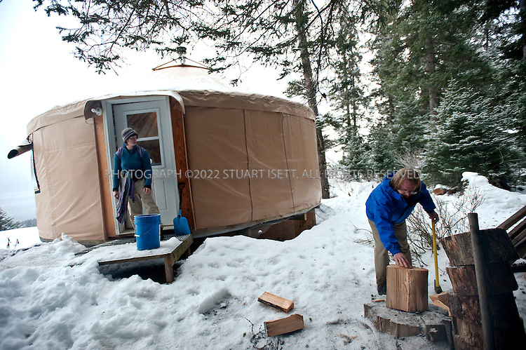 12/11/2009--Seldovia, Alaska, USA..Bretwood Higman (right), chops wood used to heat the yurt in Seldovia, Alaska while his wife Erin McKittrick looks on...The yurt is made by Nomad Shelter in Homer, Alaska, and cost about $14,000. Bretwood Higman ('Hig'), 33 and Erin McKittrick, 30, built it in November, 2008 on land owned by Hig's mother in Seldovia.The yurt is 24' in diameter, the ceiling is over 12' in the middle, 7' around the edge. It has no running water but does have electricity and internet access...McKittrick grew up in Seattle and met Higman, from Seldovia, at Carleton College in 2001. In June 2007, the couple left Seattle for the Aleutian Islands, traveling 4000 miles solely by human power through some of the most rugged terrain in the world; their adventure has recently been published in a book written by McKittrick with Hig's photographs titled, 'A Long Trek Home: 4,000 Miles by Boot, Raft, and Ski'...Together, the couple also run a small environmental non-profit, Ground Truth Trekking, which uses trekking to explore the complexities of natural resource issues. The couple lives with their 10 month old son son, Katmai, in Seldovia, Alaska, a 300 person village just off the end of the road system...©2009 Stuart Isett. All rights reserved.