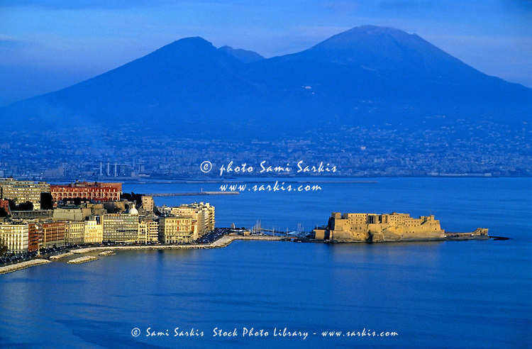 View across the Bay of Naples showing the Aragonese Castle on the peninsula of Ischia with the townscape and Mount Vesuvius in the background, Naples, Italy.