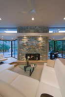 view across white sectional sofas in front of stone fireplace inset in glass wall,