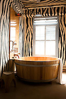 An impressive circular wooden bath tub dominates this theatrical bathroom with walls and ceiling hand-painted in a zebra stripe