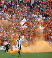 A stadium official removes a smoke bomb thrown from the stands as Houston Dynamo goalkeeper Pat Onstad and Dynamo fans clad in orange look on.  The Houston Dynamo win the MLS Cup 2006 over the New England Revolution 4-3 on penalty kicks after playing to a 1-1 tie during regulation and extra time at Pizza Hut Park in Frisco, TX on November 12, 2006.