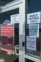 Signs on the door Tuesday, March 24, 2020, at the Benton County Clerk's office in Rogers. Early voting began Tuesday in the primary runoff election. The door was locked and only one voter was allowed into the building at a time in an effort to prevent the spread of covid-19. Early voting at the county clerk's offices in Bentonville, Rogers and Siloam Springs will continue 8 a.m. - 4:30 p.m. through March 27 and on March 30. to nwaonline.com/photos to see more photos.<br /> (NWA Democrat-Gazette/Ben Goff)