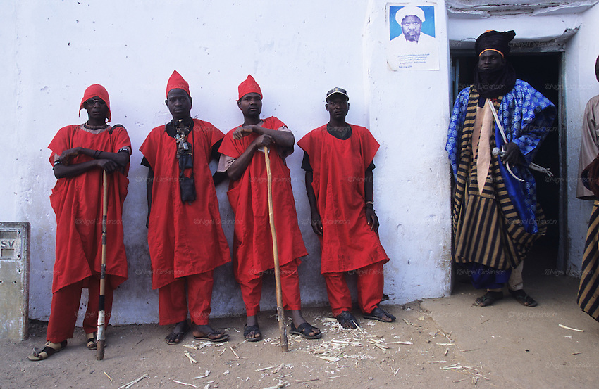 Husa Militia group get read for Fantasia Durbar celebrations..The implementation of Islamic Sharia Law across the twelve northern states of Nigeria, centres upon Kano, the largest Muslim Husa city, under the feudal, political and economic rule of the Emir of Kano. Islamic Sharia Law is enforced by official state apparatus including military and police, Islamic schools and education, plus various volunteer Militia groups supported financially and politically by the Emir and other business and political bodies. Fanatical Islamic Sharia religious traditions  are enforced by the Hispah Sharia police. Deliquancy is controlled by the Vigilantes volunteer Militia. Activities such as Animist Pagan Voodoo ceremonies, playing music, drinking and gambling, normally outlawed under Sharia law exist as many parts of the rural and urban areas are controlled by local Mafia, ghetto gangs and rural hunters. The fight for control is never ending between the Emir, government forces, the Mafia and independent militias and gangs. This is fueled by rising petrol costs, and that 70% of the population live below the poverty line. Kano, Kano State, Northern Nigeria, Africa