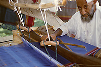 Wadi Ghul, Oman, Arabian Peninsula, Middle East - Male weaver at his loom.