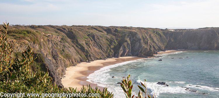Secluded sandy beach in bay between rocky headlands at Parque Natural do Sudoeste Alentejano e Costa Vicentina, Natural Park, landscape panoramic view on the Ruta Vicentina long distance walking trail, at Praia dos Machados,  Carvalhal, Alentejo Littoral, Portugal, southern Europe