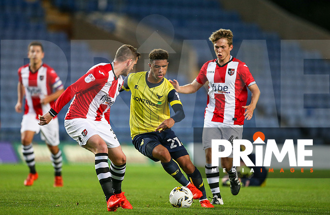 Goalscorer Tyler Roberts of Oxford United goes past Pierce Sweeney of Exeter City and Max Smallcombe of Exeter City during the The Checkatrade Trophy match between Oxford United and Exeter City at the Kassam Stadium, Oxford, England on 30 August 2016. Photo by Andy Rowland / PRiME Media Images.