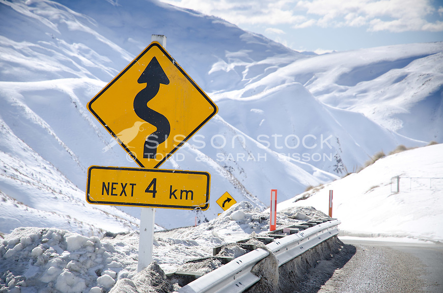 two Road signs on the treacherous Crown Range road between Queenstown and Wanaka. Winter time, snow and grit on road,  Sunny day looking down Cardona valley.