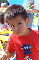 Boy age 4 looking mad at the Asian American Festival.  St Paul  Minnesota USA