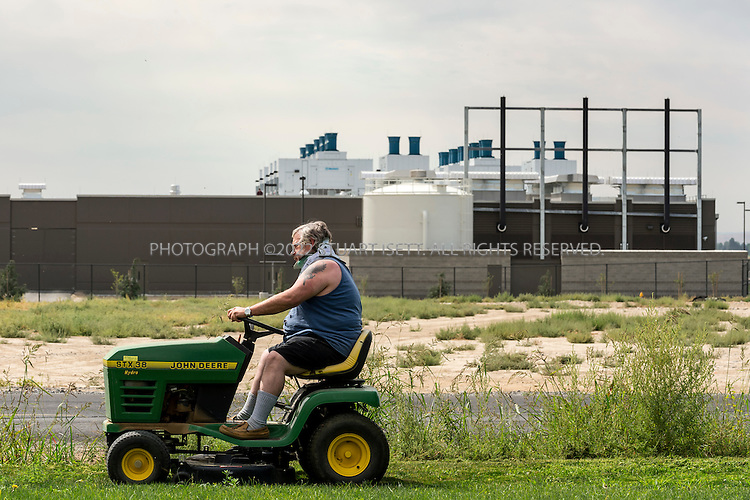 8/21/2012--Quincy, WA..Terry Razey mows his lawn in his home across from the new Sabey Data Centers in Quincy, WASH. His home is surrounded on three sides by server farms but he has refused offers for his land...Quincy has seen rapid growth of data centers, or server farms, spurred on by tax breaks and low cost electricity produced by the Grant Count PUD's nearby hydroelectric dams. Microsoft and five other companies, including Yahoo and Dell, have brought big, energy-hungry data centers to Quincy in recent years, converting former bean fields into vital hubs on the internet....©2012 Stuart Isett. All rights reserved.