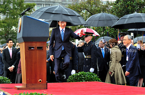 President Lee Myung-bak of South Korea hits his head on an umbrella as he walks onto the stage during an arrival ceremony on the South Lawn of the White House in Washington, D.C. on Thursday, October 13, 2011. .Credit: Kevin Dietsch / Pool via CNP