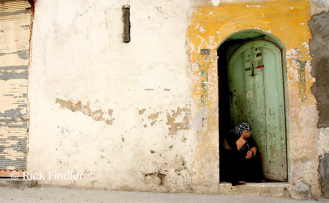 21.04.12 An elderly woman sits in a doorway in the backstreets of Armanaz, Northern Syria.