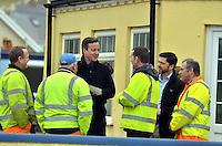 Pictured: Prime Minister David Cameron (C) speaks to Pembrokeshire Council workers who have been working to rectify the damage caused in Newgale, Pembrokeshire. Wednesday 19 February 2014<br />