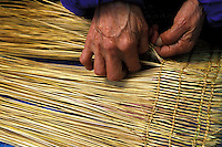 Detail of the hands of a Native Alaskan weaving a straw floor mat for use in a traditional Yupik kayak. Alaska Native Heritage Cultural Center, Anchorage, Alaska.