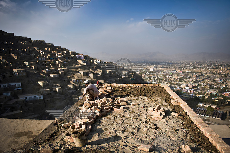 A man builds a new house with a view across the city of Kabul.