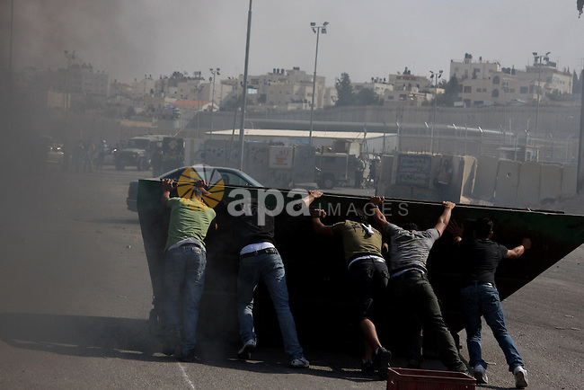 Palestinian youths take cover from Israeli border police during clashes at the Kalandia checkpoint near the West Bank city of Ramallah October 9, 2009. Palestinian leaders on Thursday called for a one-day general strike and warned of more street protests over Jerusalem, where clashes at the flashpoint al-Aqsa mosque two weeks ago cranked up tensions in the disputed city. Israel is playing down Palestinian warnings that its security tactics risk a new Palestinian uprising. Photo by Issam Rimawi