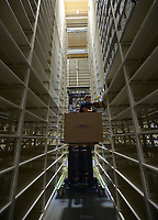NWA Democrat-Gazette/ANDY SHUPE<br /> Jared McGill, a worker with PMI Corporation in Chicago, places a box of books Friday, June 29, 2018, high on a shelf in a storage facility being constructed by the University of Arkansas for the storage of library materials south of Martin Luther King Jr. Boulevard in Fayetteville. The proper place for books in a space-starved library at the University of Arkansas, Fayetteville has become the subject of some debate after an email sent to faculty by an outgoing librarian urging them to fight against changes that are removing roughly two-thirds of printed materials.