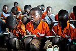 """Gota Dzongololo (center), 11, reads from the blackboard in a primary school class in Chidyamanga, a village in southern Malawi that has been hard hit by drought in recent years, leading to chronic food insecurity, especially during the """"hunger season,"""" when farmers are waiting for the harvest."""