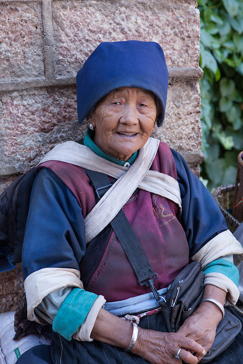 A traditional dressed Naxi woman sells her fresh vegetables on the street in Shuhe ancient town.