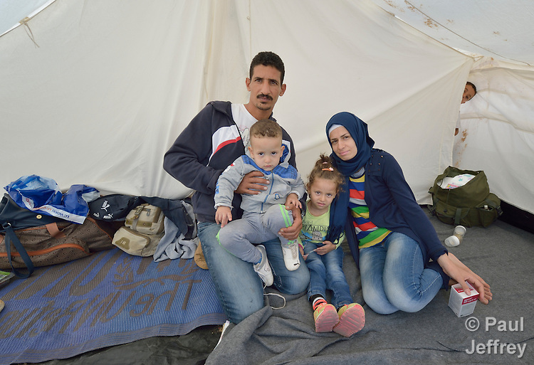 Bassem Yahiya holds his son while his wife Muhga Hamdan and daughter sit beside him. The family fled fighting in Latakia, Syria, and are sleeping in a tent in a camp for refugees on the Greek island of Chios.<br /> <br /> &quot;Life was bad. My house was bombed. There was nothing left. there was no work. There was no water. We left and spent four months in Turkey, but it was like a prison. So now we're going to Holland, where a sister and brother live. I'm going to like living in Holland,&quot; said Hamdan.<br /> <br /> The family crossed the Aegean Sea in a small boat from Turkey. They were registered and provided with food and shelter in a reception center built with support from International Orthodox Christian Charities, a member of the ACT Alliance. From Chios they will go to Athens and then on toward western Europe. Hundreds of thousands of refugees and migrants have passed through Greece in 2015.