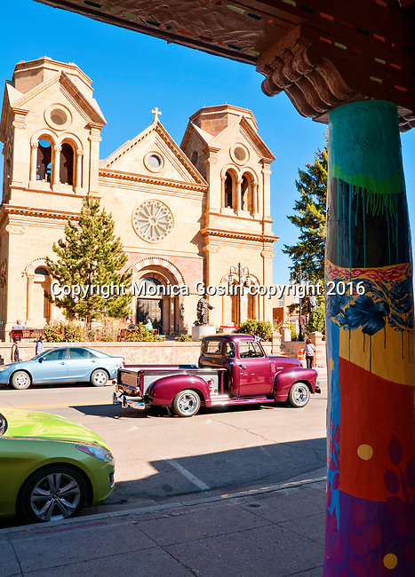Cathedral Basilica of St. Francis of Assisi on East San Francisco Street with a column of the Museum of Contemporary Native Arts in the foreground; Santa Fe, New Mexico