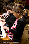 Education Elementary School Grade 2 arts enrichment music two girls and a boy playing the piano together vertical