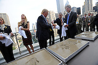 (L-r) Ivanka Trump, Donald Trump and Eric Trump clean their hands after making hand imprints in cement at the topping-off ceremony of the new 92-story tall Trump International Hotel and Tower building in Chicago, Illinois on September 24, 2008.  The building will be the tallest in North America upon its completion in six months.