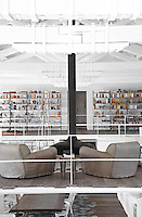 The armchairs in the sitting area created on the mezzanine walkway in the centre of the living area look over to the shelves of books and objects against the far wall