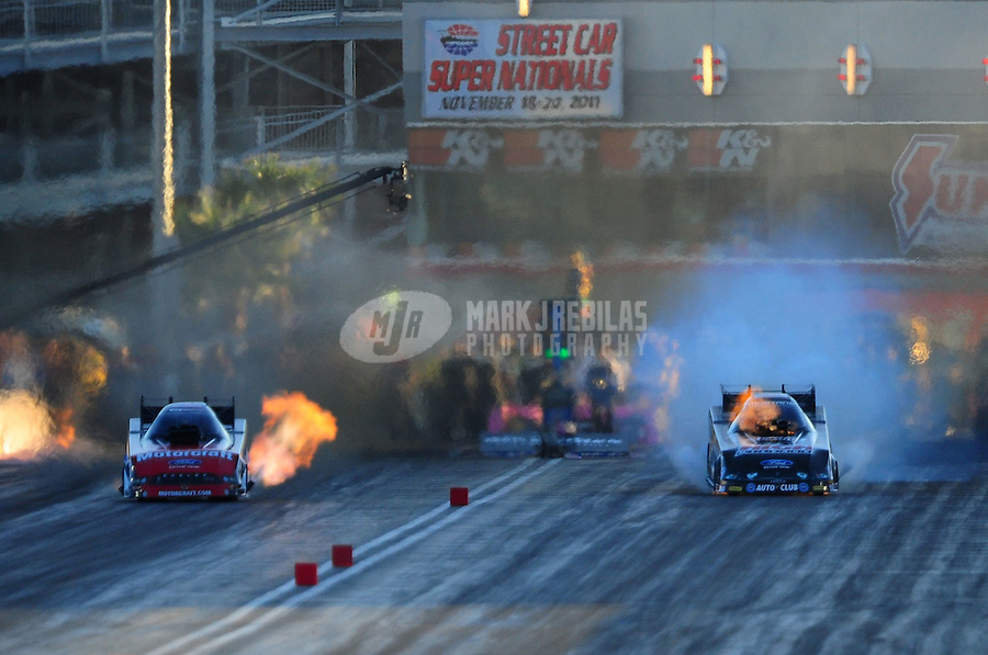 Oct. 28 2011; Las Vegas, NV, USA: NHRA funny car driver John Force (right) blows the supercharger while racing alongside Bob Tasca III during qualifying for the Big O Tires Nationals at The Strip at Las Vegas Motor Speedway. Mandatory Credit: Mark J. Rebilas-US PRESSWIRE