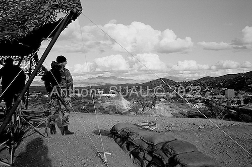 Nogales, Arizona.USA.October 24, 2006..The US National Guard watches over the border fence that separates Nogales, Mexico and Nogales USA. The fence extends for several miles in either direction off the port of entry - then there is little to stop people from crossing illegally. Nogales is flooded with Mexicans legal and illegal and is mostly a transit and shopping town.