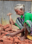 Mini Minjee breaks bricks for use in construction in the village of Suihari in northern Bangladesh.