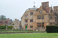 When viewed from the garden, the restored house with its large mullioned windows and ornate roof top exemplifies the Elizabethan country manor style