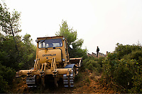 Pictured: A bulldozer tries to make way for the emergency services in Varnavas.<br /> Re: A forest fire has been raging in the area of Kalamos, 20 miles north-east of Athens in Greece. There have been power cuts, country houses burned and children camps evacuated from the area.
