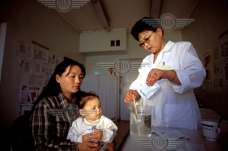© Giacomo Pirozzi / Panos Pictures..Ulaan Bator, MONGOLIA..A health worker showing a young mother how to mix oral rehydration salts, in a project sponsored by Unicef.