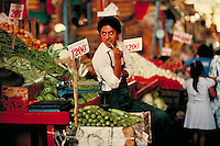 A vendor stands by his fruit stand in an open market. Cuernavaca, Mexico.