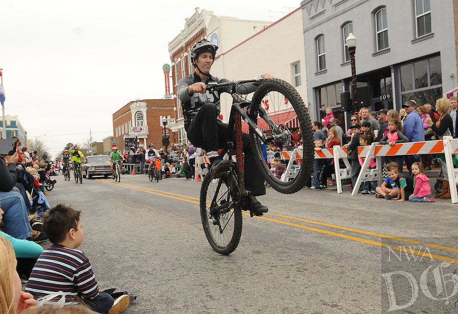 NWA Democrat-Gazette/FLIP PUTTHOFF<br /> CHRISTMAS WHEELIN'<br /> A biker rides a wheelie Saturday Dec. 12, 2015 in the Bentonville Christmas Parade through downtown Bentonville. The parade featured floats, marching bands, classic cars, Santa Claus and more. Hundreds packed the area around the square to watch the Christmas parade.