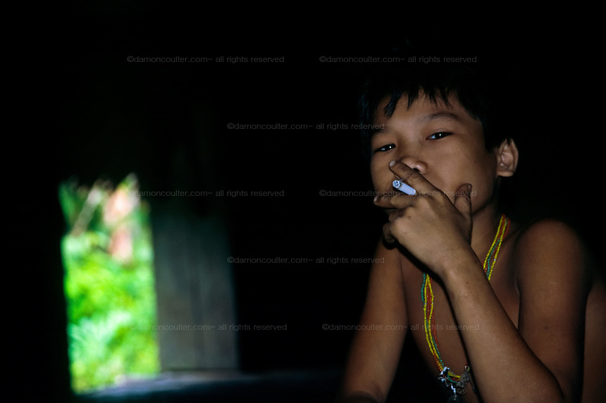 A young Mentawai boy smokes a cigarette inside an Uma or traditional forest lodge on Siberut Island, Sumatra, Indonesia, June 2000