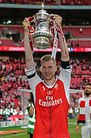 Per Mertesacker of Arsenal holds the FA Cup trophy aloft after victory in the FA Cup FINAL match between Arsenal and Chelsea at the Emirates Stadium, London, England on 27 May 2017. Photo by David Horn.