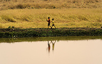 Two little children walking along a filed while their parents work