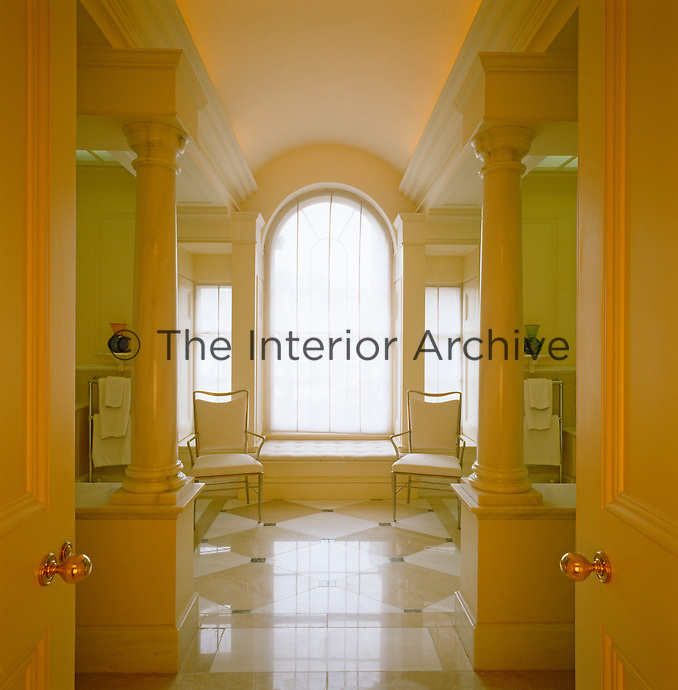 In the bathroom of a London town house an arched window takes centre stage in a design of perfect symmetry