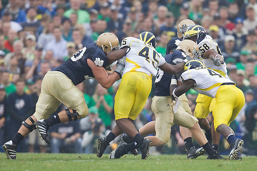 Michigan safety Cameron Gordon (#4) and linebacker Obi Ezeh (#45) make tackle on Notre Dame quarterback Nate Montana (#16) during NCAA football game between the Notre Dame Fighting Irish and the Michigan Wolverines.  Michigan defeated Notre Dame 28-24 in game at Notre Dame Stadium in South Bend, Indiana.