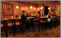 Lifestyle photography of people at the bar in Dressler's Restaurant, an upscale restaurant located mixed-use development Birkdale Village. The suburban shopping center is located in Huntersville, NC, a few miles north of Charlotte, NC.  Birkdale Village is one of the country's first mixed-use developments. The center, anchored by shopping and restaurants, was developed by Pappas Properties.