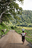 INDONESIA, Flores, a woman walks down the road in Waturaka Village carrying breakfast with tea and homey