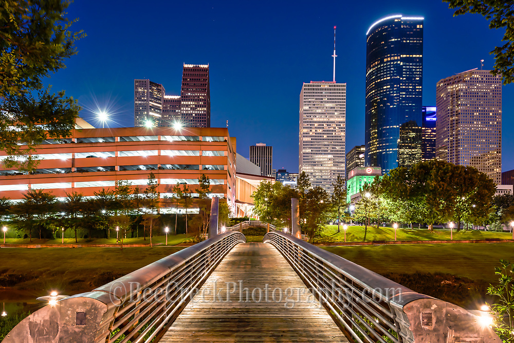 This image captures the Sabine to Bagby Promenade with the lights on the bridge with the skyline in downtown Houston. We like the way the lines down the pedestrian bridge lead you to the city skyline on the other side.  This bridge is a cross over for pedestrians and bicyles as they make their way into downtown Houston and convient for getting to the art district for plays or music events.