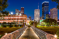This image captures the Sabine to Bagby Promenade with the lights on the bridge with the skyline in downtown Houston. We like the way the lines down the pedestrian bridge lead you to the city skyline on the other side.  This bridge is a cross over for pedestrians and bicyles as they make their way into downtown Houston and convient for getting to the theater district for plays or music events. The theater district in downtown has nine major performing groups along with six perforning halls for their art.  This pedestrian bridge lead right into the Hobby Center on the other side.  You can see some of the high rise buildings in the area and the Wells Fargo the second tallest in Houston is looming in this skyline view from the pedestrian Sabine bridge.This bridge allows you to cross over the Buffalo Bayou and it is well lit a night so for those that want to ride their bikes in for a play or just to walk along the banks of the bayou after dark when it cools down.