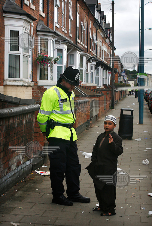 A policeman talks to a young boy after the killing of three men: 21 year old Haroon Jahan, and brothers Shazad Ali (30) and Abdul Musavir (31) who were killed on Tuesday evening in a hit and run incident by suspected looters as they guarded a petrol station forecourt with many other people on Dudley Road in the Winson Green area of Birmingham, which was hit by a surge of rioting and looting. The violence started in London on Saturday evening after a peaceful protest in response to the shooting by police of Mark Duggan during an attempted arrest escalated into a riot, but has now spread to other areas in the country.