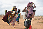 A mother and her children--newly arrived refugees--carry their belongings through the Dadaab camp in northeastern Kenya. Already the world's world's largest refugee settlement, Dadaab has swelled in recent weeks with tens of thousands of recent arrivals fleeing drought in Somalia. The Lutheran World Federation, a member of the ACT Alliance, is manager of the camp, and in July opened a new extension to begin housing the newest refugees.