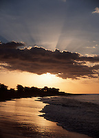 April 23rd, 2004-Oecussi, Timor-Leste-The setting sun's rays burn past some clouds as it eliminates the golden beaches of Oecussi town (also known as Pante Macassar), in Oecussi District.  Oecussi is home to the sight where the Portuguese first stepped out of their boats onto Timorese soil in around 1515.  Photograph by Daniel J. Groshong/Tayo Photo Group.