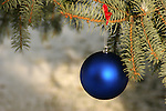 Outside Christmas ball ornament hanging on a Evergreen Christmas Tree in winter